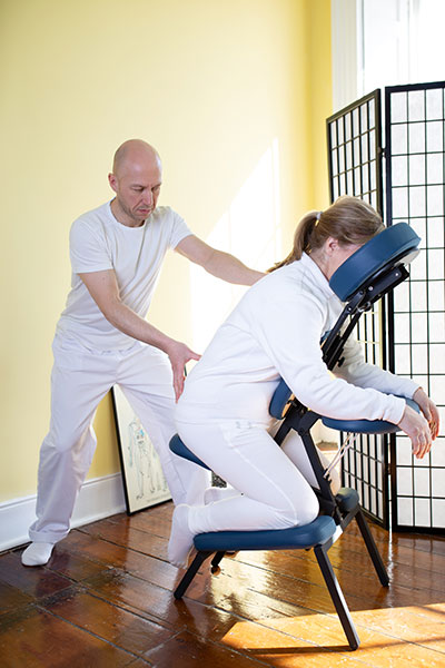 man giving an OnSite Seated Shiatsu treatment to woman on chair